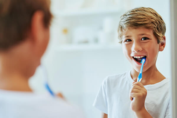 A boy brushing his teeth in front of a mirror