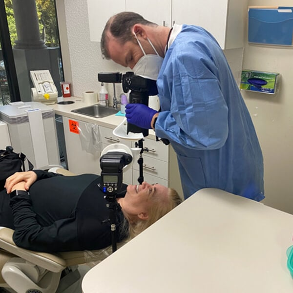 Dr. Cohen taking a photo of the smile of a patient who is lying in the dentist's chair
